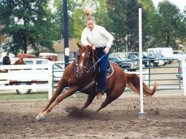 My daughter Lindsay sliding around a pole on her horse Jake